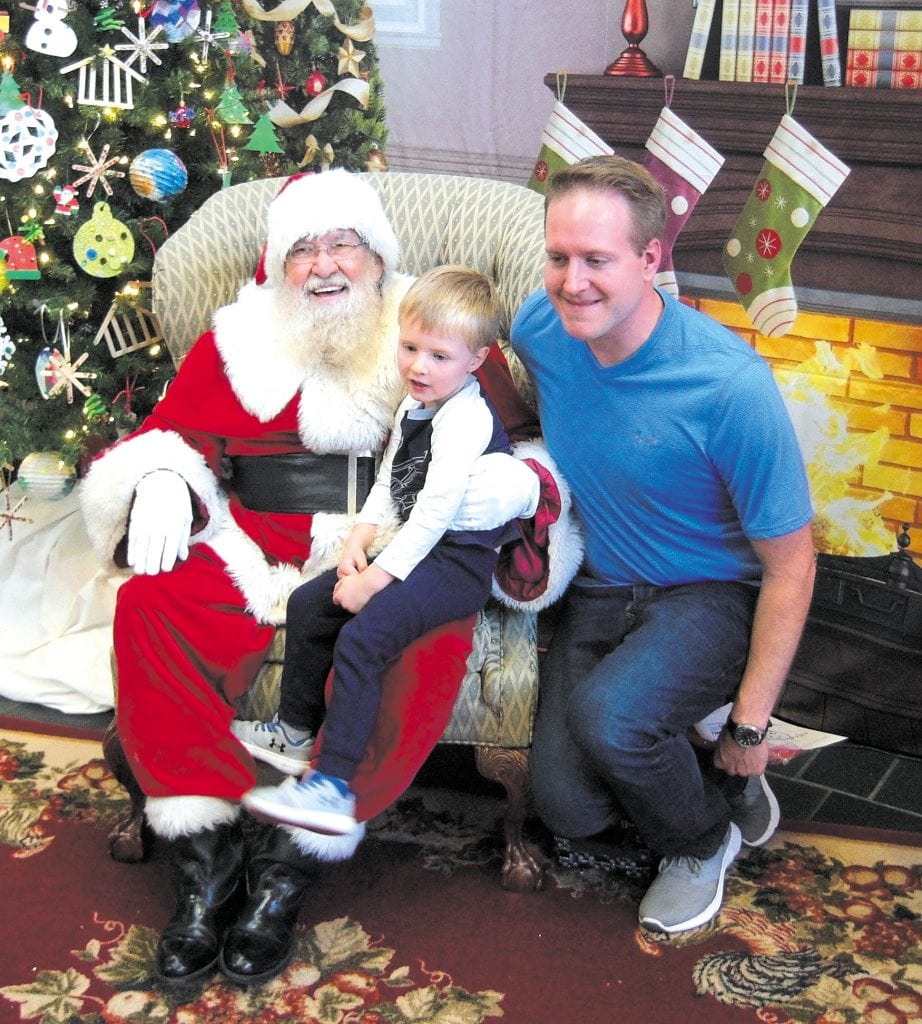 Ward 2 Alderman Justin Charboneau and his son pose with Santa Ted at Christmas in Crestwood in 2017.