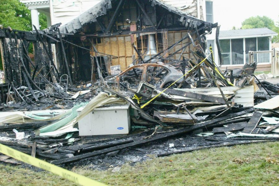 The remnants of a garage and a car inside it destroyed in a fire Monday, seen the day after the fire.