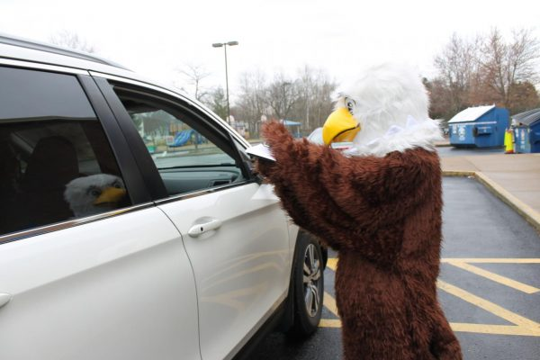 The Point Eagle mascot passes out Chromebooks at a drive-thru event in March 2020.