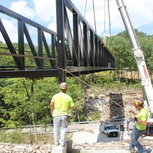 Workers lower one of the largest pedestrian trail bridges in St. Louis County into place at Cliff Cave Park in Oakville in July.