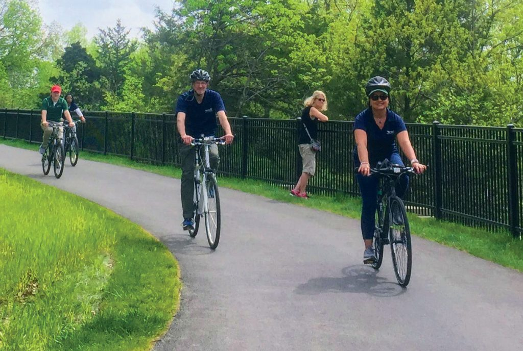 Bicyclists enjoying the paved path at the new Cliff Cave Trail in 2018. Bikers also have the option of an unpaved trail.