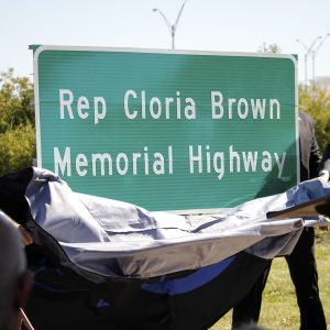 Legislators from both parties unveil the 'Cloria Brown Highway' Lindbergh sign