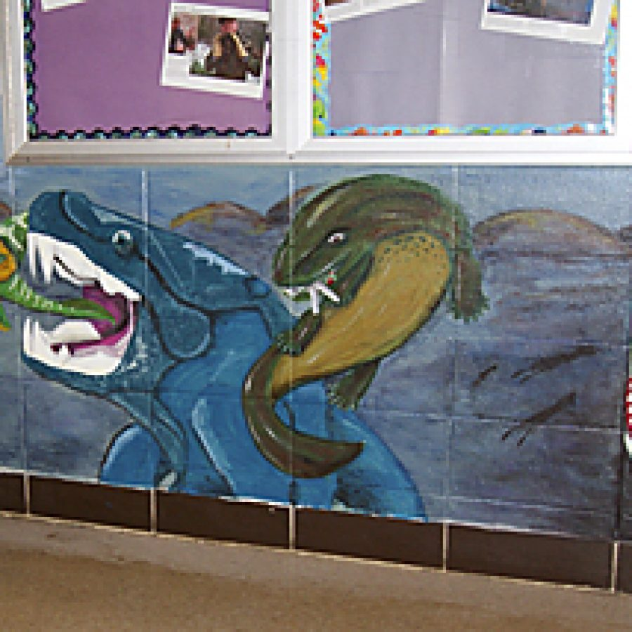 Cody Summers, a 2011 Oakville Senior High School graduate, is shown with the mural he spent the last semester of his senior year designing and creating that will have a lasting impact on his high school and future classes of Oakville science students.