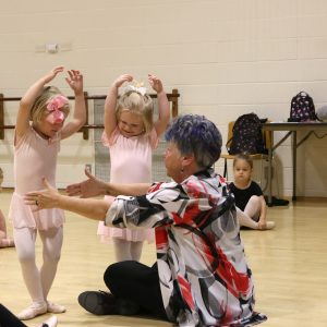 Among the many classes held by Crestwood Parks and Recreation at the Community Center this summer were children's ballet classes. Above, Sandy Book teaches cousins Caroline Kulik, left, and Audrey Flesch a relieve during the preschool ballet, tap and jazz class. The cousins are wearing matching bows. Photo by Jessica Belle Kramer.