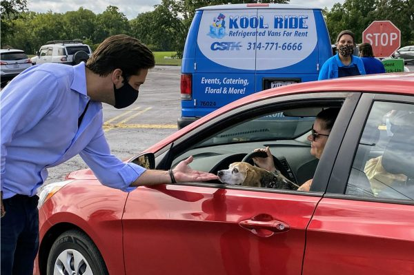 Rep. David Gregory, R-Sunset Hills, left, greets a member of the public and her dog at a food distribution event at Mehlville High School hosted by Gregory and Rep. Jim Murphy Sept. 3, 2020.