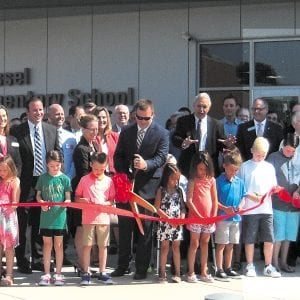 Lindbergh Schools Board of Education members, administrators, teachers and staff gathered last week along with former school board members, state and local elected officials, community leaders and members of the Dressel family to celebrate the opening of the district's 650-student Dressel Elementary School, as Dressel students cut the ribbon for the new state-of-the art school on the direction of Superintendent Jim Simpson, arms extended. Photo by Mike Anthony.