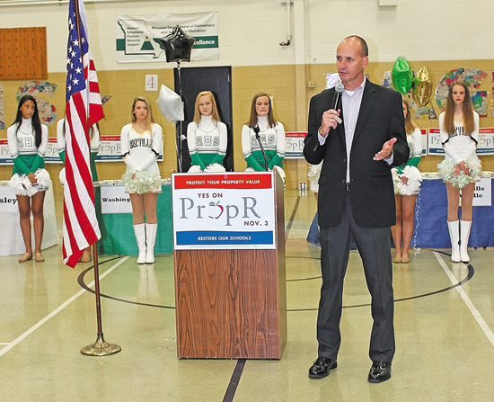 Pictured above, Superintendent Chris Gaines asks supporters at a 2015 rally for Prop R to help him get out the vote so that he can hire reading coaches and keep experienced teachers in the district. Behind him are the Mehlville High School Pantherettes and the Oakville High School Golden Girls.