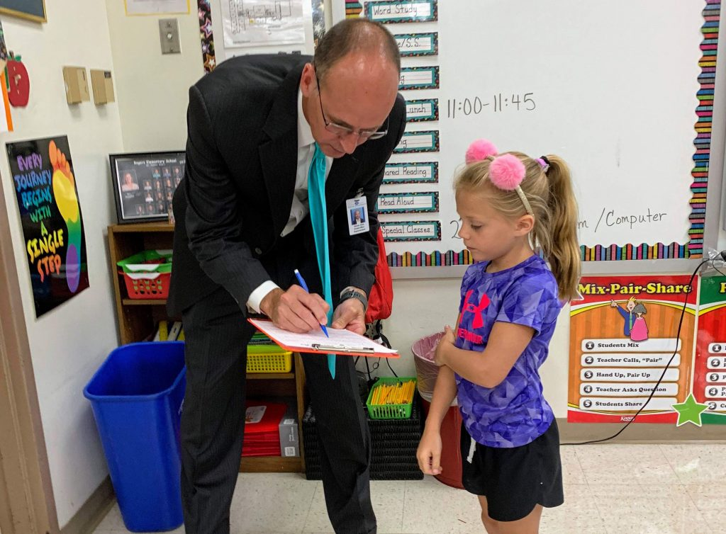 In+the+Rogers+Elementary+first-day-of-school+scavenger+hunt+in+2019%2C+second-grader+Aleah+Jacobsmeyer%2C+right%2C+and+other+students+went+straight+to+the+top+for+help%2C+asking+Superintendent+Chris+Gaines+if+he+fit+any+of+their+categories.+He+checked+the+box+%E2%80%98I+like+vegetables.%E2%80%99+