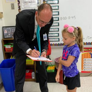 In the Rogers Elementary first-day-of-school scavenger hunt in 2019, second-grader Aleah Jacobsmeyer, right, and other students went straight to the top for help, asking Superintendent Chris Gaines if he fit any of their categories. He checked the box 'I like vegetables.'