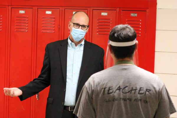 Mehlville Superintendent Chris Gaines talks to a teacher in a hallway while schools were all-virtual in fall 2020.