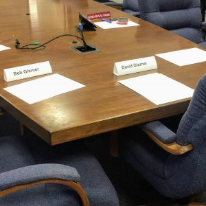 The nametags of Bob and David Glarner in front of their empty chairs at the Ethics Committee hearing. Photo by Gloria Lloyd.