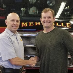 Mehlville Fire Protection District Capt. Ty Cardona, left, shop steward of Mehlville Local 2665 of the International Association of Fire Fighters, shakes hands with Board of Directors Chairman Aaron Hilmer, signaling a new era of cooperation between the union, the board and district administration.