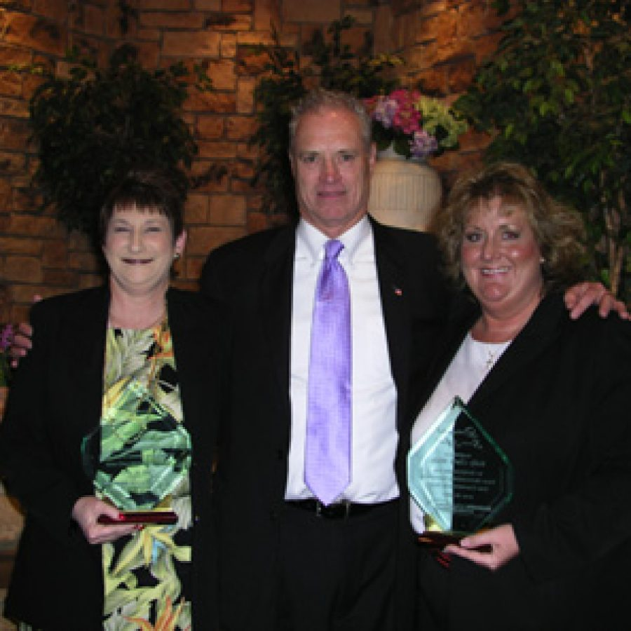 Interim Superintendent Jerry Chambers presents the school district's prestigious Distinguished Service Award to Gail Schmitt, left, and Kelly Clark Wicks at Mehlville's 27th annual Recognition Night.