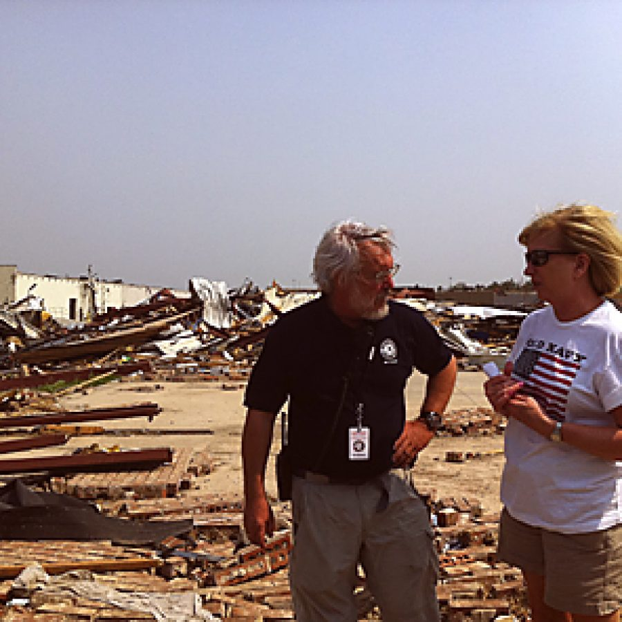 Bruce Bailey, executive director of AmeriCorps St. Louis, discusses the relief ef-forts under way in Joplin with Rep. Marsha Haefner of Oakville.