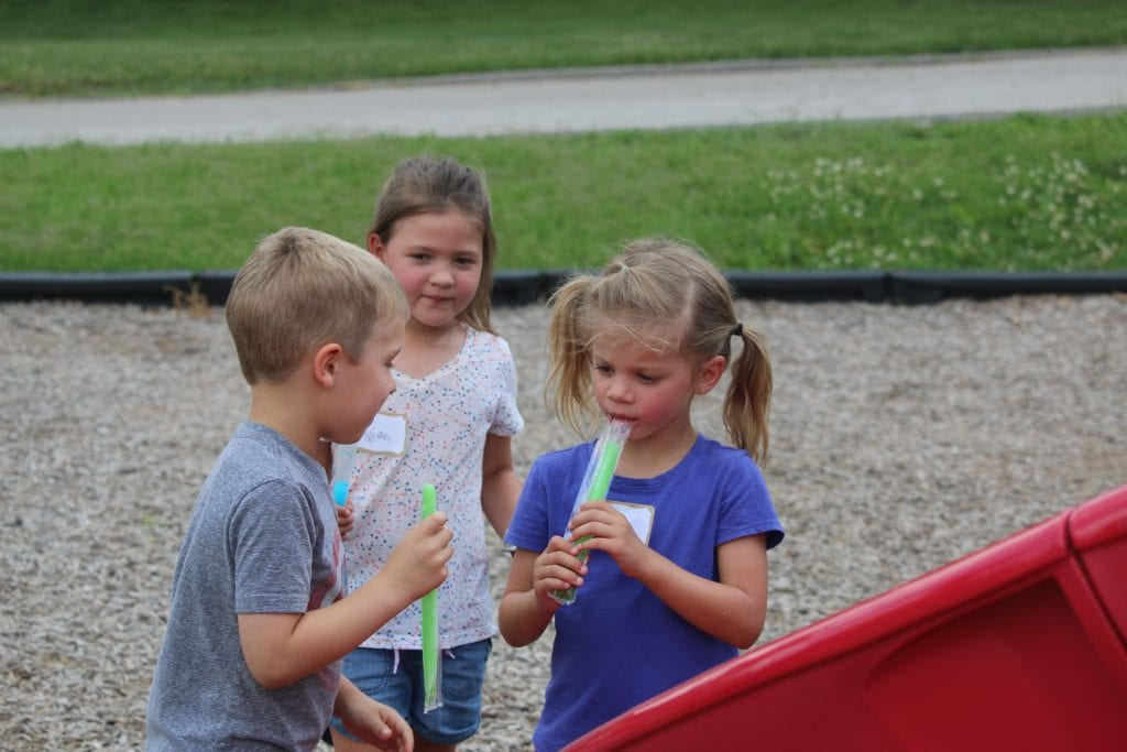 Incoming Kennerly kindergarteners Andrew and Hailey enjoy the Popsicles that Principal Todd Morgan handed out.