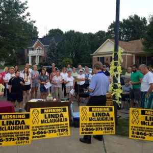 Linda McLaughlin's pastor, Joel Christianson, center in blue, leads attendees at a candlelight vigil last fall in a prayer for her safe return. Photo by Gloria Lloyd.