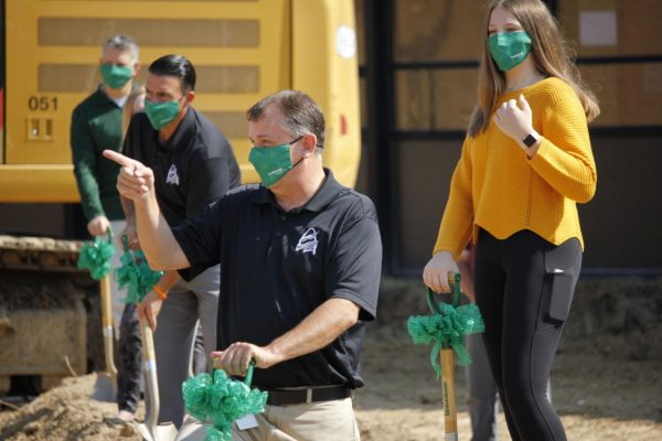 Ninth grade class president Carrie Maschmann, right, and school board President Mike Shamia, second from left, shovel dirt with Superintendent Tony Lake.