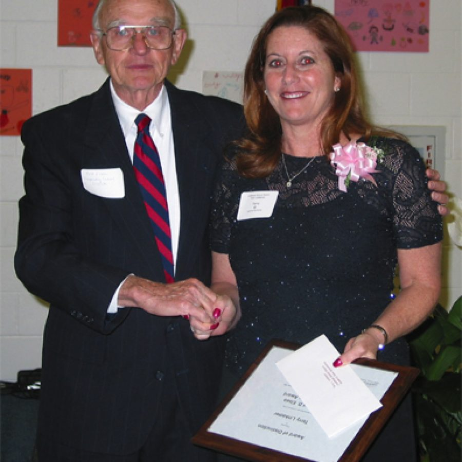Terry Linkemer, right, receives the Robert D. Elsea Scholarship Award from Elsea, who served as executive director of the Cooperating School Districts for 21 years.
