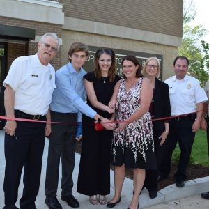 From left, MFPD Community Education Officer Jim Hampton; Dr. Bosche's children Jacob and Jennifer Bosche; his wife, Amy; MFPD board Treasurer Bonnie Stegman; MFPD Chief Brian Hendricks; and St. Louis County Police Officer Michael Costa cut the ribbon for the new Dr. Christopher Bosche EMS Training Facility May 22.