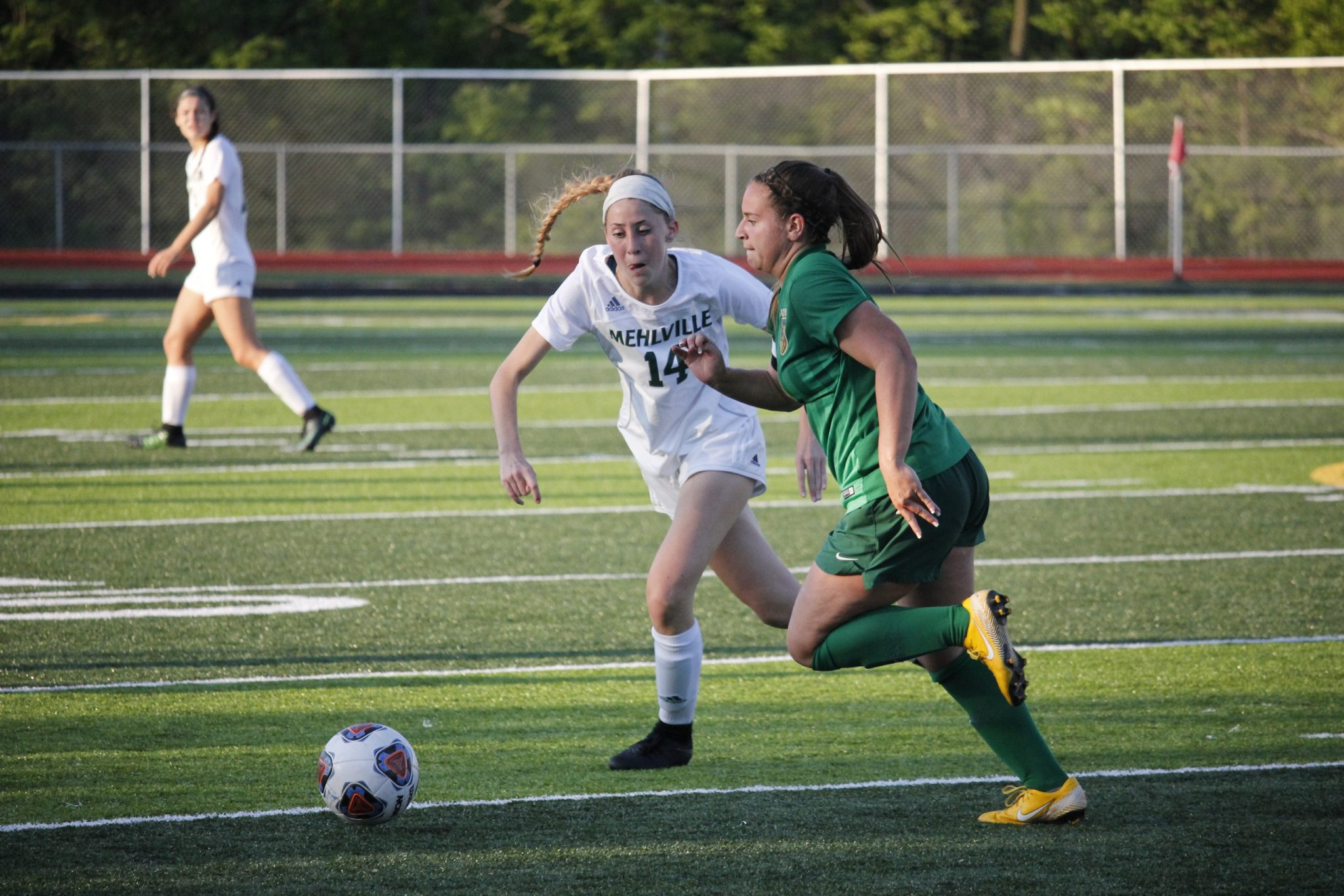 Mehlville midfielder Abigial Miller, junior, races after the ball alongside Lindbergh midfielder and captain of the team, Carly Boccardi, senior, during a game at Oakville High School May 15. With Lindbergh's 1-0 overtime win, the team will advance to sectionals against Jackson High School May 21. Photo by Erin Achenbach.