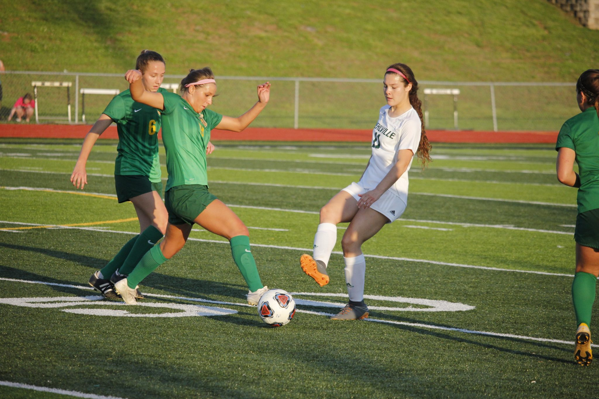 From left; Lindbergh midfield Meghan Baudendistel, senior, and Lindbergh defender Payton Husman, senior, protect the ball from Mehlville forward Grace Ledbetter, junior, during a game at Oakville High School May 15. Lindbergh topped Mehlville 1-0 in overtime. Photo by Erin Achenbach.