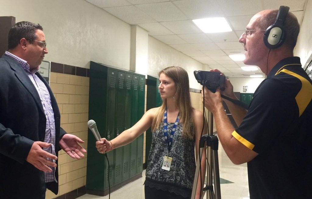 Oakville+High+journalism+teacher+Jeff+Kuchno%2C+right%2C+holds+the+camera+while+OHS+student+Hannah+Hoffmeister%2C+middle%2C+interviews+local+lawyer+Mark+Haefner+after+Haefner%E2%80%99s+speech+in+support+of+Mehlville+School+District%E2%80%99s+Proposition+R+at+a+Sept.+8%2C+2015+rally.+Photo+by+Gloria+Lloyd.