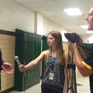 Oakville High journalism teacher Jeff Kuchno, right, holds the camera while OHS student Hannah Hoffmeister, middle, interviews local lawyer Mark Haefner after Haefner's speech in support of Mehlville School District's Proposition R at a Sept. 8, 2015 rally. Photo by Gloria Lloyd.
