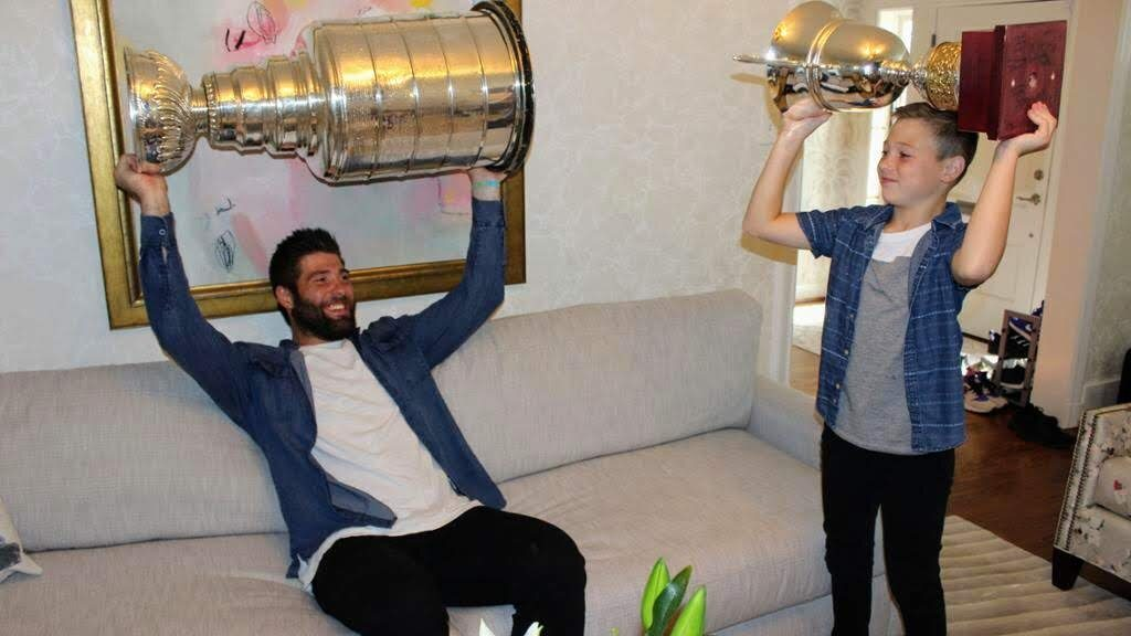 Blues player Pat Maroon started off his day with the Stanley Cup by taking photos with his family at his home in Clayton. Maroon then paid a visit to All American ice rink in Green Park, where St. Louis County Police officers, including Green Park Officer Jeremy Hake, posed for photos with Maroon and Stanley. After eating toasted raviolis from the Cup at Charlie Gitto's on The Hill, Maroon then finished the day on a lake to the west of St. Louis with family and friends, and a private concert from country star Adam Sanders.