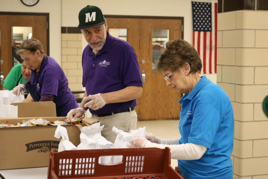 Mehlville School District employees, seen above March 23, are handing out grab-and-go meals of breakfast and lunch to all children living in the Mehlville School District during the extended closure. The meals are available at seven sites.