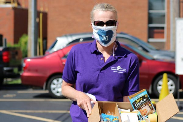A Mehlville School District employee hands out emergency food boxes from Operation Food Search to students receiving grab-and-go meals while students are out of school during the pandemic.