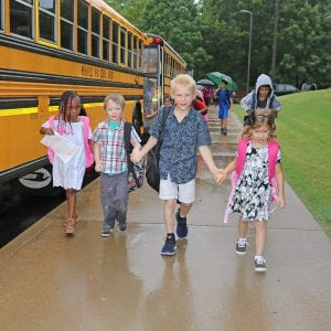 Oakville Elementary students Baileigh Holland, Logan Woods, Tommy Schoen and Hanna Backs walk into school together on the first day in 2018.