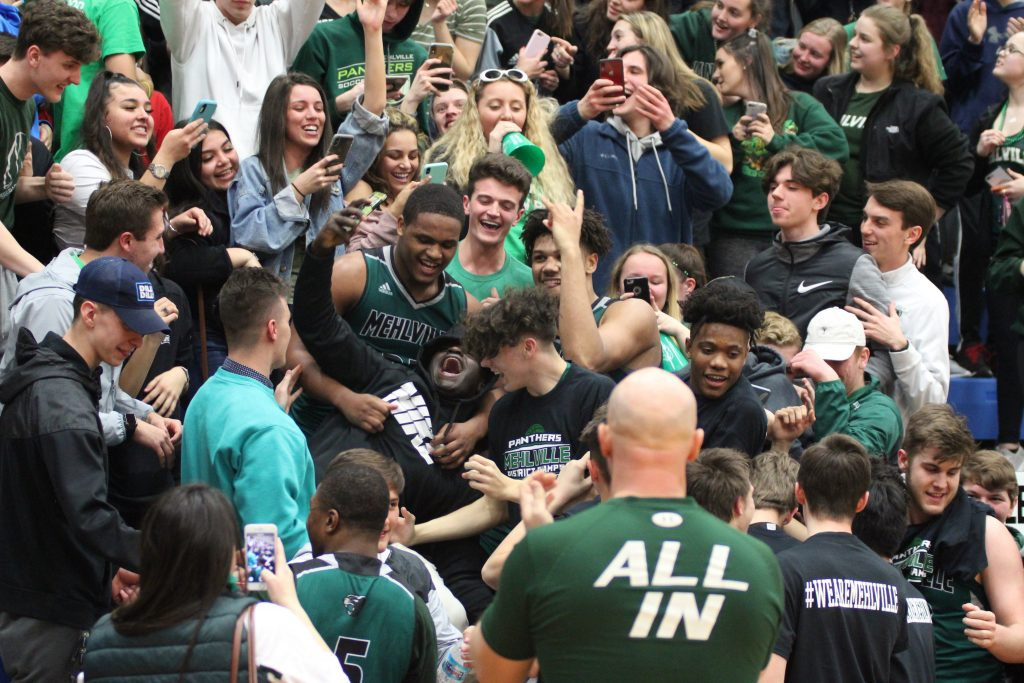 It was pandemonium after the Mehlville High School Panthers boys basketball team won the sectional championship versus Jackson in Hillsboro to make the state's Elite Eight in March 2019 . After wading into the crowd to celebrate their win, Mehlville's King Waller and Davion Bradford take selfies with fans. The team went on to lose in the state quarterfinals that year against CBC.
