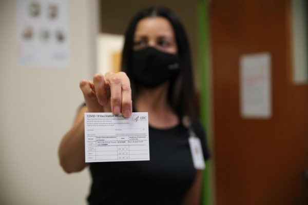 Mercy Hospital South Chief Medical Officer Dr. Aamina Akhtar displays a COVID-19 vaccination card, which states where and when an individual received the COVID-19 vaccine. The Pfizer vaccine requires two doses administered roughly three weeks apart.