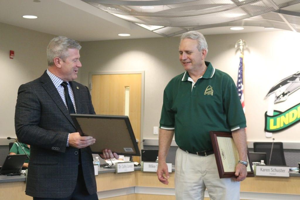 Rep. Doug Beck, D-Affton, presents a legislative commendation to retired Lindbergh Superintendent Jim Simpson in June 2018.