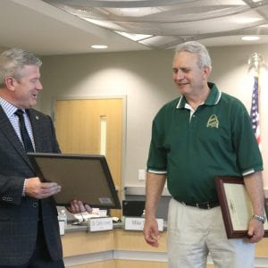 Rep. Doug Beck, D-Affton, presents a legislative commendation to retired Lindbergh Superintendent Jim Simpson in June 2018.