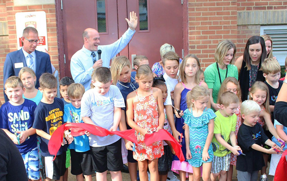 Mosaic+Elementary+Principal+Scott+Clark%2C+hand+raised%2C+leads+the+students+of+the+new+school+in+chanting+%22We+are+Mosaic%22+before+they+cut+the+ribbon+of+the+new+school+Aug.+14.