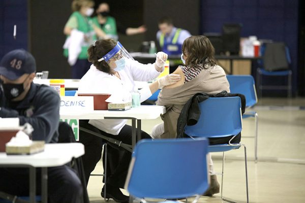 Members of the Visiting Nurses Association, National Guard, county employees and volunteers help administer the vaccine at the mass vaccination site in Ferguson Tuesday, Feb. 2, 2021. The county announced Tuesday that in addition to the mass vaccination site at the Florissant Valley campus of St. Louis Community College, additional vaccination sites would open in the Mehlville, Affton and Eureka fire protection districts, which will begin administering vaccines to eligible members of the public who have appointments Thursday.
