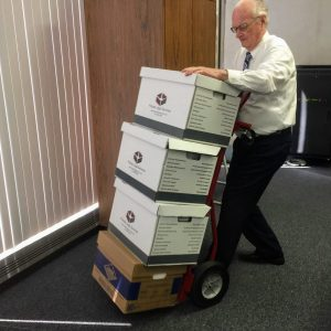 Black Jack Mayor Norm McCourt, who works in the county clerk's office, transports the four boxes filled with an estimated 7,000 pages of documents from the Glarner brothers about the county's Northwest Plaza lease to the county's vault for storage after an Ethics Committee hearing June 25. Photo by Gloria Lloyd.