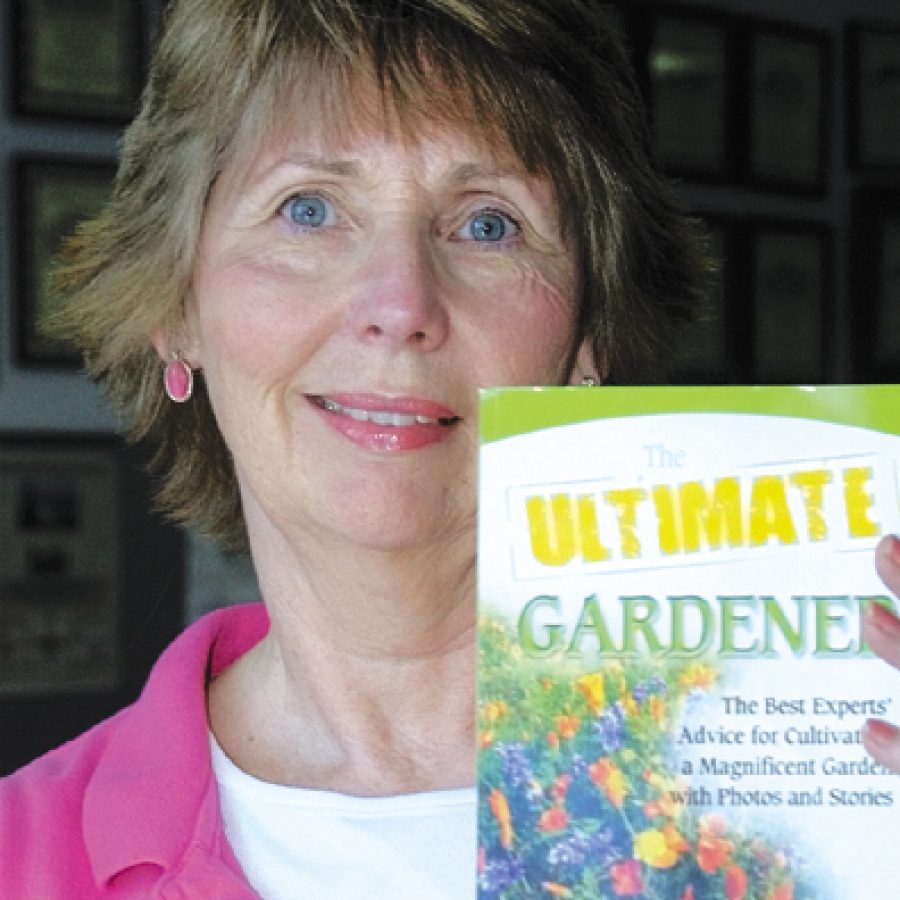 Linda O'Connell displays a copy of 'The Ultimate Gardener,' which features her story 'Grandpa's Garden.'