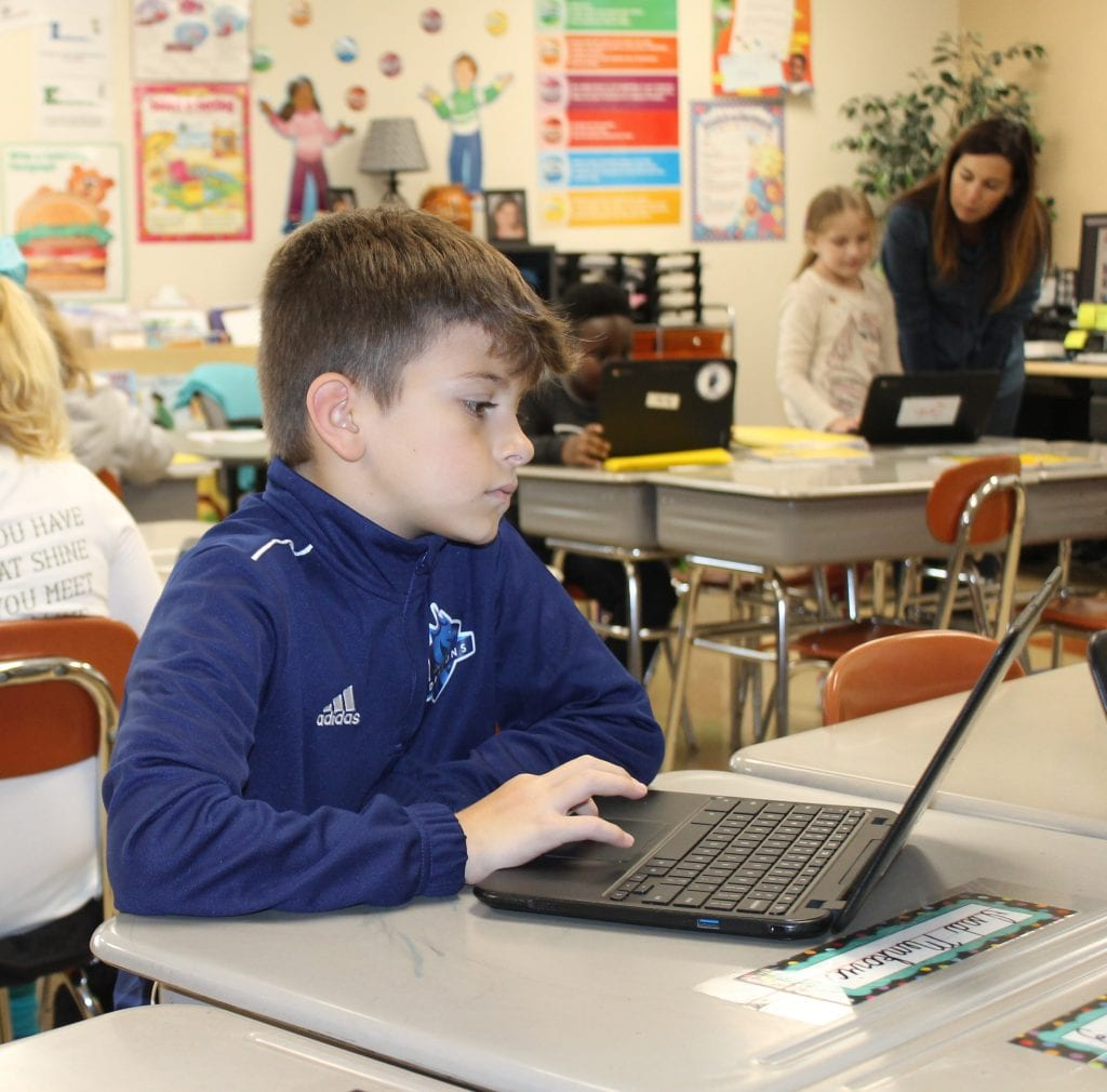 Isad Menkovic, a third-grade student at Oakville Elementary, completes a math lesson.