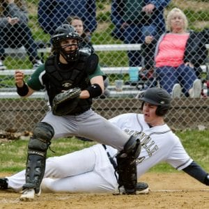 Oakville's Hunter Iffland slides home safely as Mehlville catcher Carmen Fuller awaits the throw from his defense in a March 2019 game. Photo by Bill Milligan.
