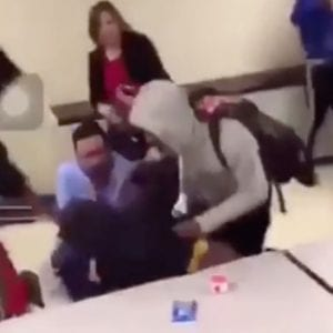 This screenshot taken from a blurry video a student posted to Snapchat Monday shows Oakville High Principal Jan Kellerman, top, intervening in a fight along with who appears to be Assistant Principal Casey Olearnick, in a blue shirt at the bottom. Assistant Principal Brian Brennan is on the ground in the dark blue shirt.