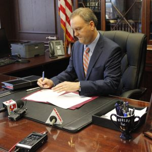 County Executive Sam Page signs ethics reform executive orders into law Sept. 18 in the county executive's office. Photo by Erin Achenbach.