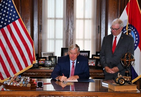 Gov. Mike Parson, above left, signs the legislation for nursing home cameras into law in July as bill sponsor Rep. Jim Murphy of Oakville, right, looks on.