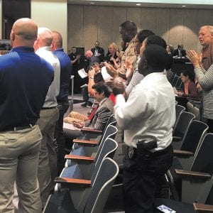 Police officers and the mother of three police officers, right, give a standing ovation to the County Council at the Oct. 17, 2017 meeting after the council unanimously agreed to give preliminary approval to raises for the St. Louis County Police Department approved by voters through Proposition P. Photo by Gloria Lloyd.
