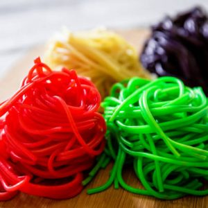 Color pasta on wooden plate on white table. Tasty vegetarian food