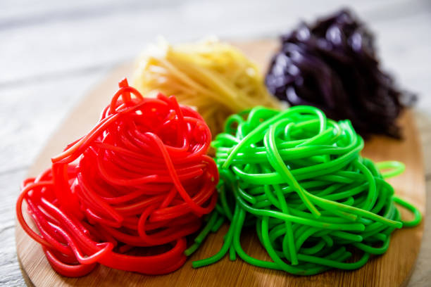 Color+pasta+on+wooden+plate+on+white+table.+Tasty+vegetarian+food