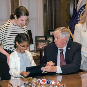 Gov. Mike Parson signs HB 397 and hands the signed bill to the daughter of Rep. Mary Elizabeth Coleman.  Also pictured is Sen. Jeanie Riddle.