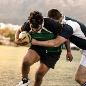 Professional rugby players striving to get the ball during the game. Rugby player with ball is blocked by the opposite team player at ground.