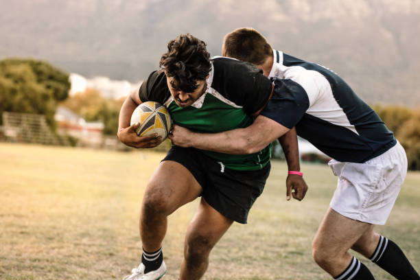 Professional+rugby+players+striving+to+get+the+ball+during+the+game.+Rugby+player+with+ball+is+blocked+by+the+opposite+team+player+at+ground.